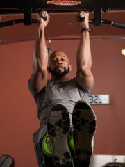 Kennis Sewell does a pull up with his legs straight out, making it incorporate his abdominal muscles.