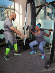 Always the trainer, Kennis helps Erica with her weighted squats.