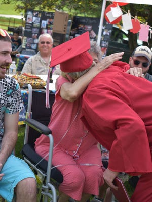 Riverheads High School senior Westley Swinson hugs his grandmother, Ruby Swinson, during an informal graduation ceremony on April 29 attended by family, friends and school administrators, including Riverheads High principal Max Lowe.