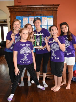 Six SWFL girls with Think Tank pose with well-earned medals and a trophy inside Carlson's home on May 5, 2017. They plan to compete in the Odyssey of the Mind World Finals in late May.