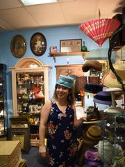 Reporter Ashley Collins tries on vintage hats at Chesterdales' Home & Garden in Naples.