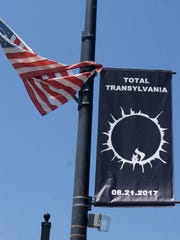 A banner advertising the solar eclipse with the signature white squirrel hangs in downtown Brevard.