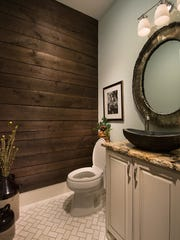 The half-bath has reclaimed wood along the walls.
