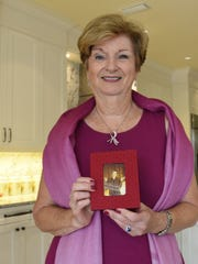 Georgia Hitzke holds a photo of her best friend, Nicki Ewing, who died from breast cancer at age 56. Hitzke is the executive director of Susan G. Komen Southwest Florida and works to help raise awareness and fund research for breast cancer.