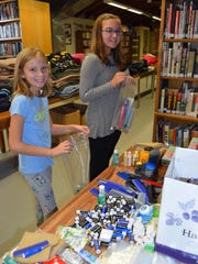 Zoe Jenkins of Elmer and Sophia Petronglo of Pittsgrove stuff bags with personal items like combs, lip balm, antibacterial wipes, toothpaste and deodorant.