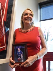 Shelly Church holds a photo of her son Kyle Fernstrom, who died at age 18 from a congenital heart defect. Her office at Raymond James in Naples houses dozens of plaques, photos and mementos of her and Kyle's work with the American Heart Association. Church has made it her mission to raise money for the Collier County Heart Walk and this year reached a million-dollar milestone.