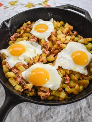Eggs top a cast-iron skillet full of smoked salmon hash.