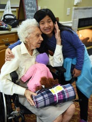 Halls Elementary Student Council member Sophia Elkins receives a hug from Elmcroft resident Trula Chapman.