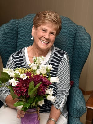 Barbara Morris holds the beautiful floral arrangement she received as one of her gifts as Mom of the Year.