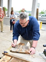 Ken McMahon with City of Knoxville's Community Development Department, signs the piece of wood that was cut at the ribbon cutting ceremony at Smoky Mountain Vintage Lumber.