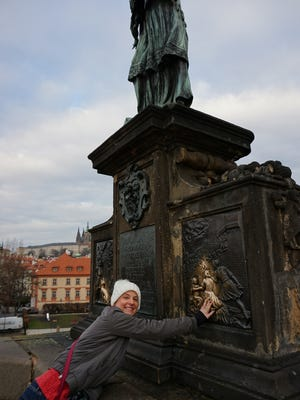 Carrie Bryniakm, independent agent for Must Love Travel, at the statue of St. John Nepomuk in Prague, Czech Republic. It is said that those that touch the statue will return to Prague at another point in their lives. Bryniakm is the Cocoa Beach Chamber of Commerce's Business Champion of the Month.