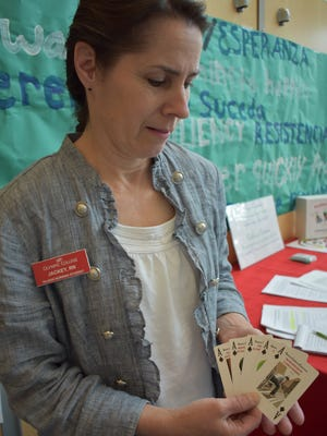 Jackey Kirsh, a bachelor of science in nursing candidate at Olympic College, displays cards from the Resilience Trumps ACEs card game that Olympic College nursing students shared with students at James A. Taylor High School in North Mason. The cards give students an opening to talk about traumatic life events, such as the incarceration of a loved one.