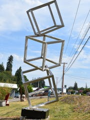 "Sculptor James Kelsey's piece, ""Cubes (Cubed),"" is"