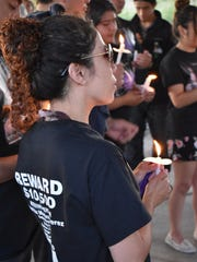 Angelica Castillo holds a candle at a vigil Monday