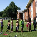 Children line up to ride a water slide during the 11th annual back-to-school bash at the John B. Hughes apartments in Springfield, Mo. on July 31, 2015.