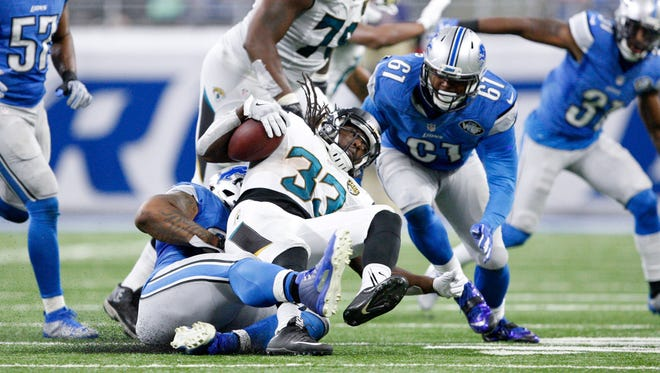 Jacksonville Jaguars running back Chris Ivory gets tackled by Detroit Lions defensive tackle Stefan Charles and defensive end Kerry Hyder (61) during the fourth quarter Nov. 20, 2016, at Ford Field.
