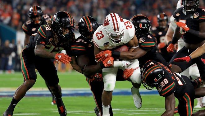 Jonathan Taylor tries to squeeze through the Miami defense during last season's Orange Bowl.