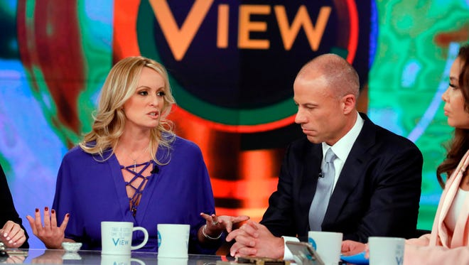Adult film actress Stormy Daniels, left, with her attorney Michael Avenatti appear on the daytime talk show 'The View,' Tuesday, in New York. Daniels released a composite sketch of the man she says threatened her in a Las Vegas parking lot to stay quiet about her past sexual tryst with President Donald Trump. Avenatti says they are offering $100,000 for information leading to the man's identification.