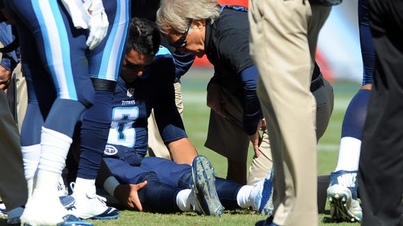 Oct 18, 2015; Nashville, TN, USA; Tennessee Titans quarterback Marcus Mariota (8) talks with team trainer Burton Elrod after an injury during the first half against the Miami Dolphins at Nissan Stadium. Mandatory Credit: Christopher Hanewinckel-USA TODAY Sports