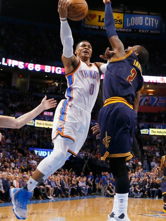 Oklahoma City Thunder guard Russell Westbrook (0) shoots in front of Cleveland Cavaliers guard Kyrie Irving (2) during the first half of an NBA basketball game in Oklahoma City, Thursday, Feb. 9, 2017. (AP Photo/Sue Ogrocki)