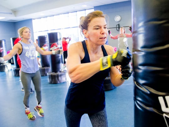 Alyssa Oldham of Altoona, left, does jumping jacks while her workout partner, Nikki Hedrick, of Runnells punches the boxing bag at the Altoona Campus in this file photo from January 2018.