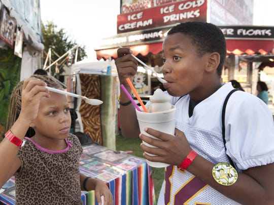 Brooklyn Mathews,7, tries to steal a taste of a root beer float her brother Chase, 11, is having at the Tulare County Fair in Tulare on Wednesday, September 16, 2015.