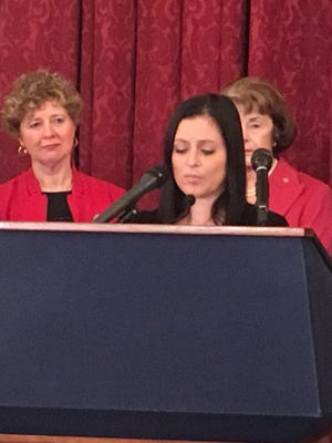 Olympic gold medalist Dominique Moceanu speaks at a Capitol Hill news conference about legislation to protect amateur athletes from abuse. Rep. Susan Brooks, R-Ind., and Sen. Dianne Feinstein, who are standing behind Moceanu, are lead sponsors of the bill.