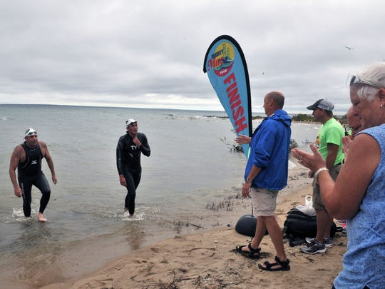 Peter Gutenberg, 41, left, of San Diego, and Brent Augustine, 28, of Ferndale, emerge from Lake Huron, Monday, Sept. 7, 2015, after a 5.7-mile swim from Michigan's Upper Peninsula. The inaugural Mighty Mac Swim had 84 open water swimmers traverse the Straits of Mackinac during the annual Labor Day Mackinac Bridge Walk, and fundraiser for Habitat for Humanity.
