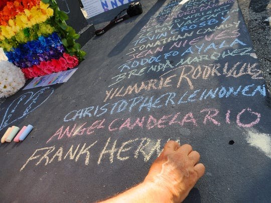 Edwin Rodriguez writes the names of the  victims of
