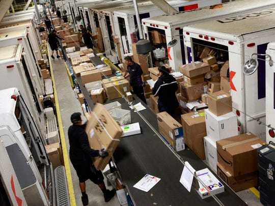 FedEx worker Alejo Pasion unloads packages from an airplane container to a conveyor belt for tagging, sorting and delivery during the holiday shopping season. (Laura A. Oda/Bay Area News Group/TNS)