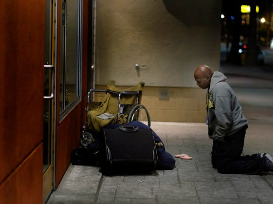 Anthony Ruffin, 48, kneels to speak with a homeless man as he sleeps on the sidewalk in Hollywood, Calif. (Francine Orr/Los Angeles Times/TNS)