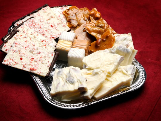 A selection of candies, including peppermint bark, fine chocolates, and toffee.