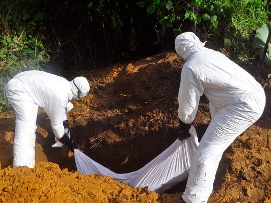 Health workers bury a man who was  suspected of contracting