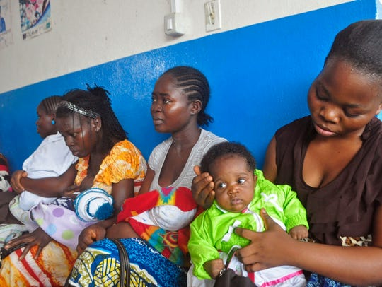 Mothers wait inline for their children to be vaccinated