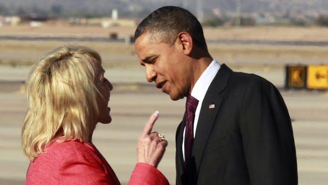 """Arizona Gov. Jan Brewer points at President Barack Obama after he arrived at Phoenix-Mesa Gateway Airport, Wednesday, Jan. 25, 2012, in Mesa, Ariz. Brewer greeted Obama and what she got was a book critique. Of her book. The two leaders engaged in an intense conversation at the base of Air Force Oneís steps. Both could be seen smiling, but speaking at the same time. Asked moments later what the conversation was about, Brewer, a Republican, said: """"He was a little disturbed about my book."""" Brewer recently published a book, """"Scorpions for Breakfast,"""" something of a memoir that describes her years growing up and defends her signing of Arizonaís controversial law cracking down on illegal immigrants, which Obama opposes. Brewer also handed Obama an envelope with a handwritten invitation for Obama to return to Arizona to meet her for lunch and to join her for a visit to the border.  (AP Photo/Haraz N. Ghanbari)"""