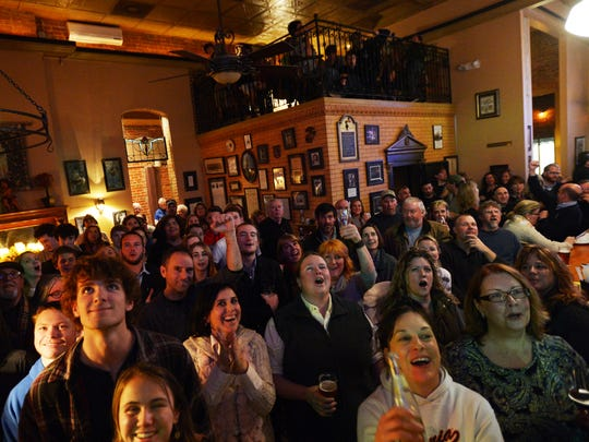 """Attendees at a """"Jeopardy!"""" viewing party celebrate as Broadwater teacher Eric Hack responds correctly to a clue during the show on Tuesday, Feb. 4, 2015 in Cape Charles, Va. Hack won the round and will advance in the show's Teachers Tournament."""