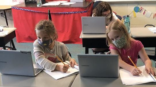 Grain Valley elementary students at their laptops during summer school in July. The district says it will start the school year on Sept. 8, with middle school and high school students on a hybrid learning plan for at least the first month.
