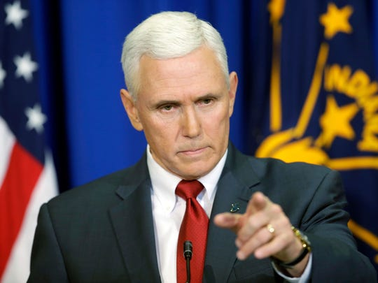 Then-Indiana Gov. Mike Pence takes a question during