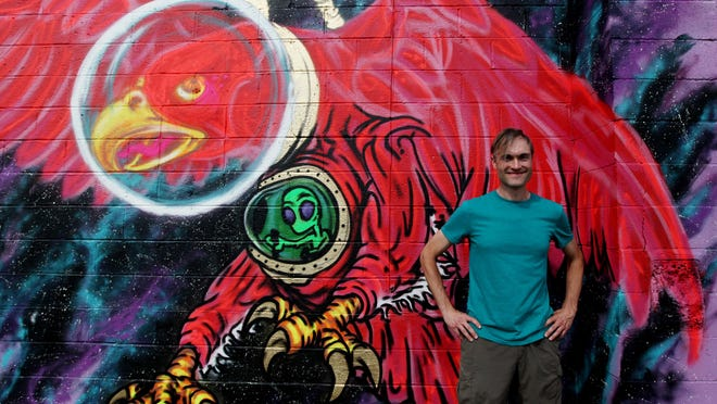 Ian MacRae, owner of E-N Computers in Waynesboro, watches as the walls of his building are transformed into works of art during the Virginia Street Arts Festival on Saturday, August 29, 2015 on Commerce Street in Waynesboro.