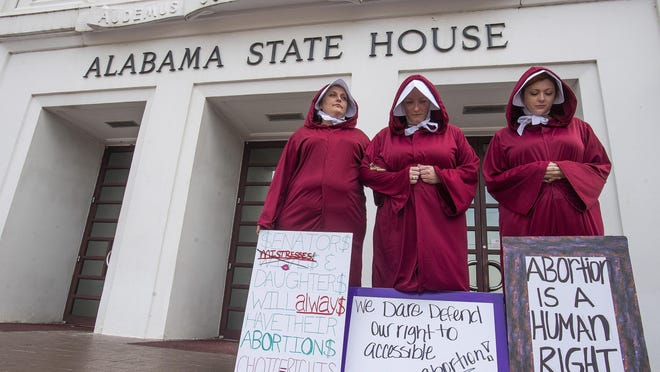 FILE - In this April 17, 2019, file photo, Bianca Cameron-Schwiesow, from left, Kari Crowe and Margeaux Hartline, dressed as handmaids, protest against a bill banning nearly all abortions at the Alabama State House in Montgomery, Ala. As abortion opponents cheer the passage of fetal heartbeat laws and other restrictions on the procedure, abortion-rights groups have been waging a quieter battle in courthouses around the country to overturn limits on providers. (Mickey Welsh/The Montgomery Advertiser via AP, File)