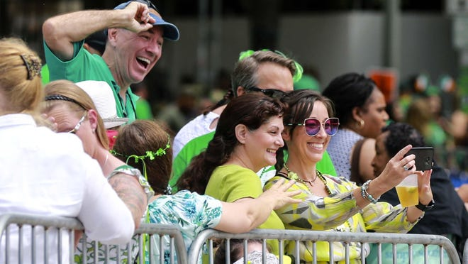 Spectators take selfies at the St. Patrick's Day Parade Saturday, March 16, 2019 in Delray Beach.