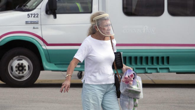 A customer wearing a face shield leaves the Dollar Tree on Okeechobee Boulevard in West Palm Beach Wednesday. County commissioners voted Tuesday to require masks be worn in public places.