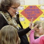 Rosemary Martin, a longtime physical education teacher at Heyworth Elementary School in Heyworth, Ill., high-fives second-grader Kamryn Whitwood in the school gym during a P.E. class. Martin has a long-standing practice of integrating heart health lessons into P.E. class. Steve Smedley/The Pantagraph via AP