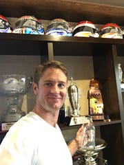 Ryan Hunter-Reay poses in front of his Borg-Warner trophy holding the empty bottle of winning milk.