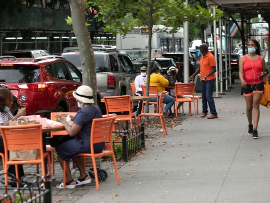 People dine at outside tables at Junior's Restaurant in the Brooklyn borough of New York.