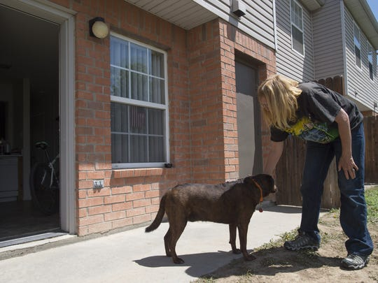 Twila Freel pets her dog, Ratchett, outside of her new townhome on Wednesday, May 31, 2017. Freel, who was homeless for 10 years, is enjoying life at home after securing housing.