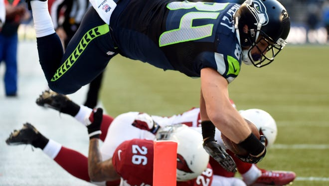 Cooper Helfet #84 of the Seattle Seahawks dives to score a 20 yard touchdown passed by Russell Wilson #3 in the third quarter against the Arizona Cardinals during their game at CenturyLink Field on November 23, 2014 in Seattle, Washington.  (Photo by Steve Dykes/Getty Images)