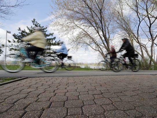 Cyclists bike along the Fox River Trail  in De Pere.