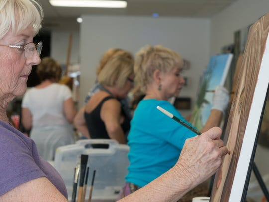 Barbara Lenox-Oates works on a painting at Create Art