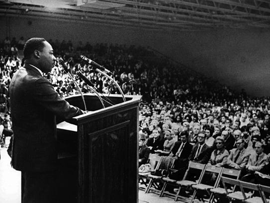 Martin Luther King Jr., addresses a crowded gymnasium